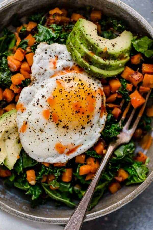Overhead shot of Kale and Sweet Potato Sauté in a bowl with a fried egg on top and avocado slices.