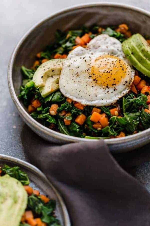 Photo take from an angle of the Kale and Sweet Potato Sauté in a bowl with a fried egg on top and avocado slices.