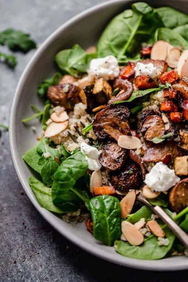 Overhead photo of the Balsamic Roasted Vegetables with Quinoa Salad served over greens and topped with toasted almonds and goat cheese.