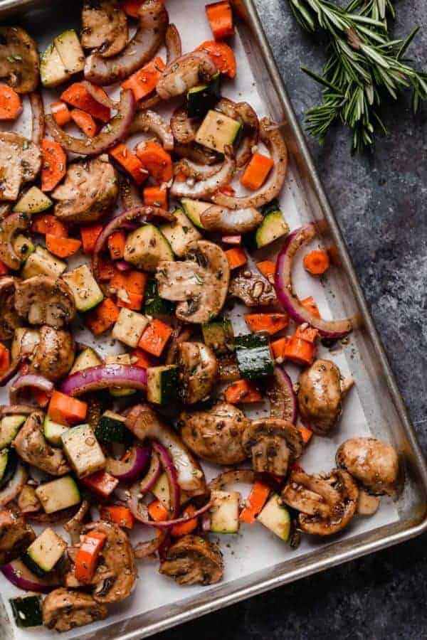 A sheet pan of a variety vegetables prepped for roasting for the Balsamic Roasted Vegetable with Quinoa Salad. Overhead shot.