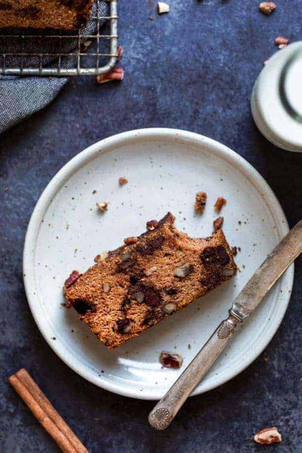 Overhead view of a Pumpkin Chocolate Chip Bread slice missing a bite on a white plate with a knife laying next to it