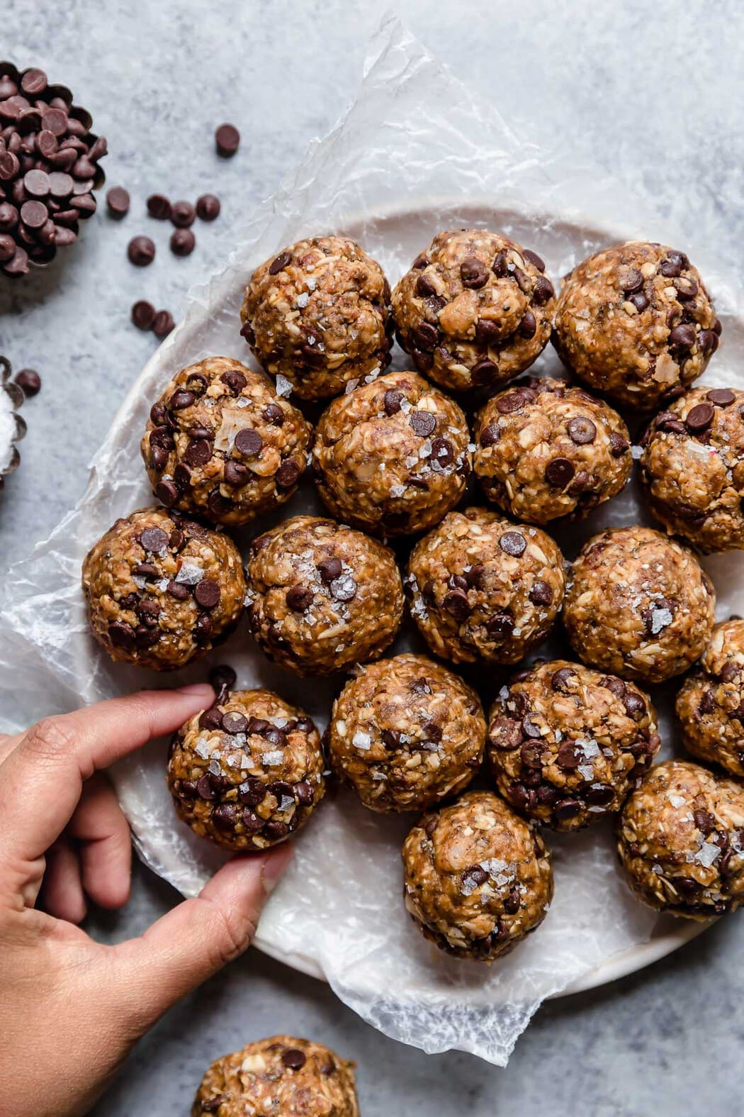 Peanut Butter Oatmeal Balls on a platter with a hand grabbing one of the bites.