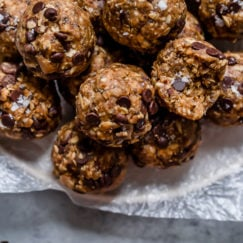 A parchment covered serving platter piled high with chocolate chip peanut butter oatmeal energy bites