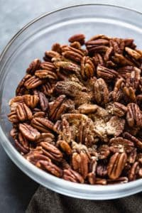 Pecans in a clear glass bowl with maple syrup and cinnamon on top