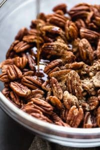 Pecans with maple syrup drizzled on top ready for baking