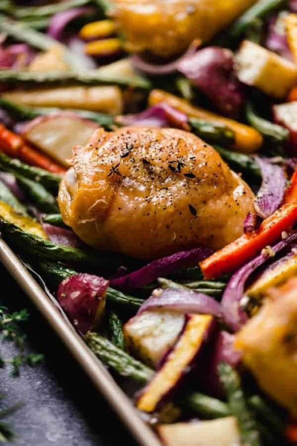 Perfectly roasted chicken thigh topped with fresh herbs on a bed of roasted vegetables on a sheet pan .