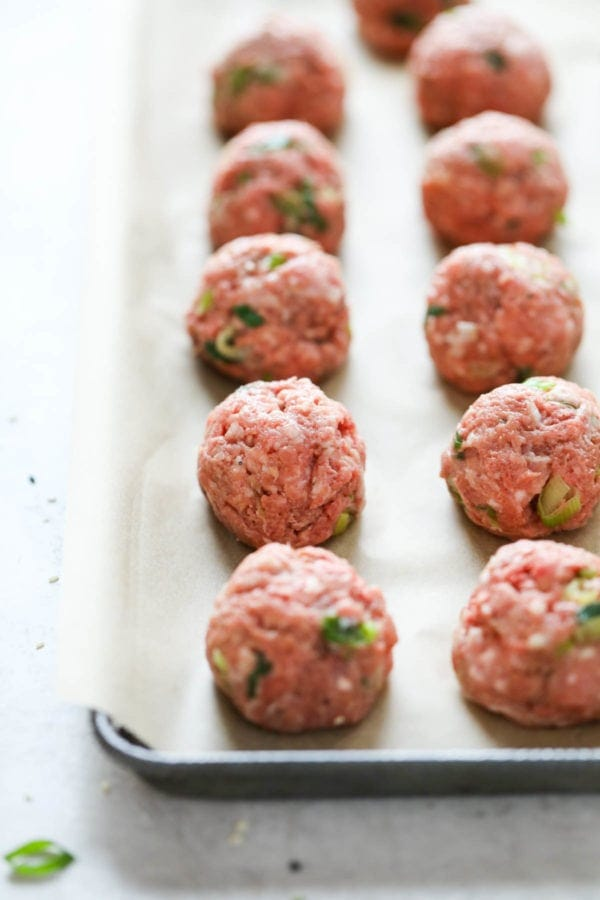 Perfectly rolled teriyaki meatballs lined up on a parchment covered baking sheet ready for baking