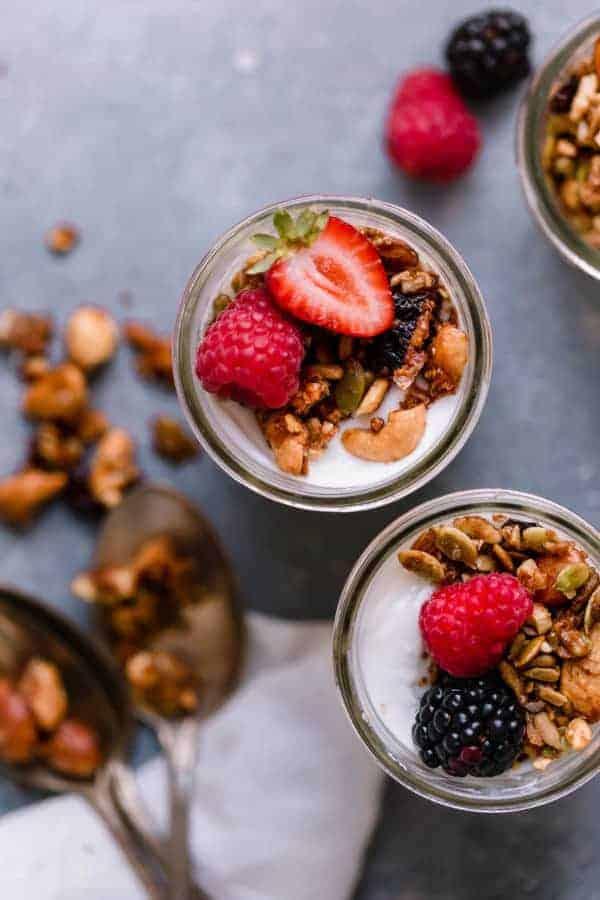 Overhead shot of Paleo Granola in glass cups on top of yogurt with raspberries, strawberries and blackberries.