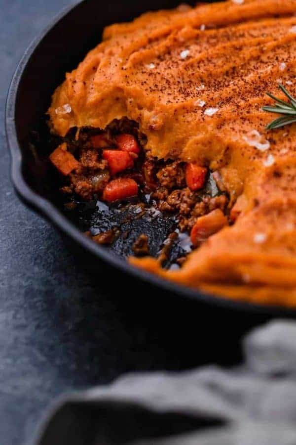 Close up view of shepherd's pie topped with creamy sweet potatoes and sprinkled with sea salt flakes and chili powder