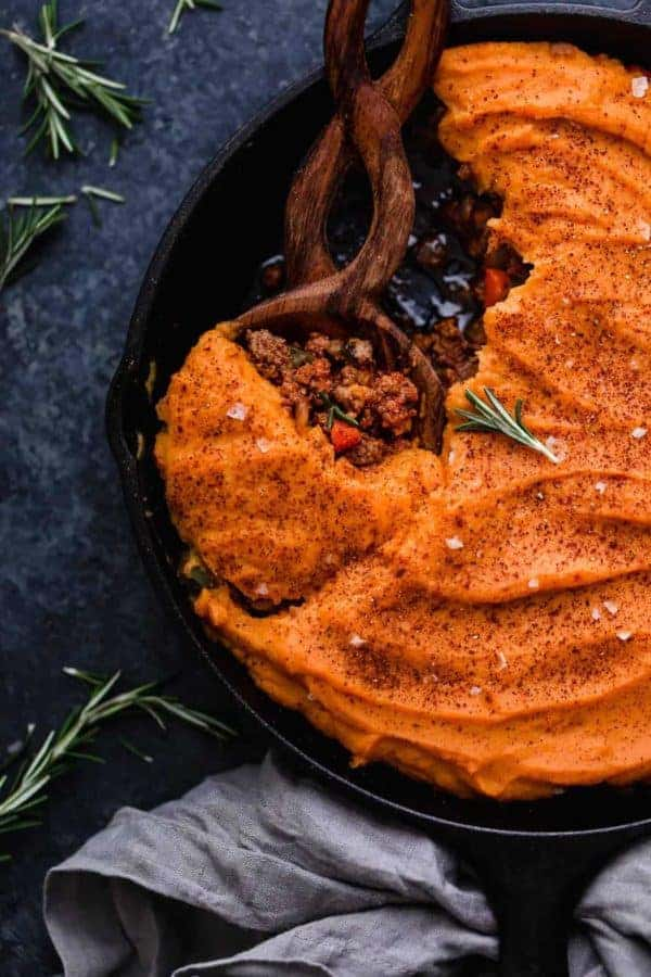Photo of Shepherd's Pie with Sweet Potato Topping in a cast iron with a wooden serving spoon.
