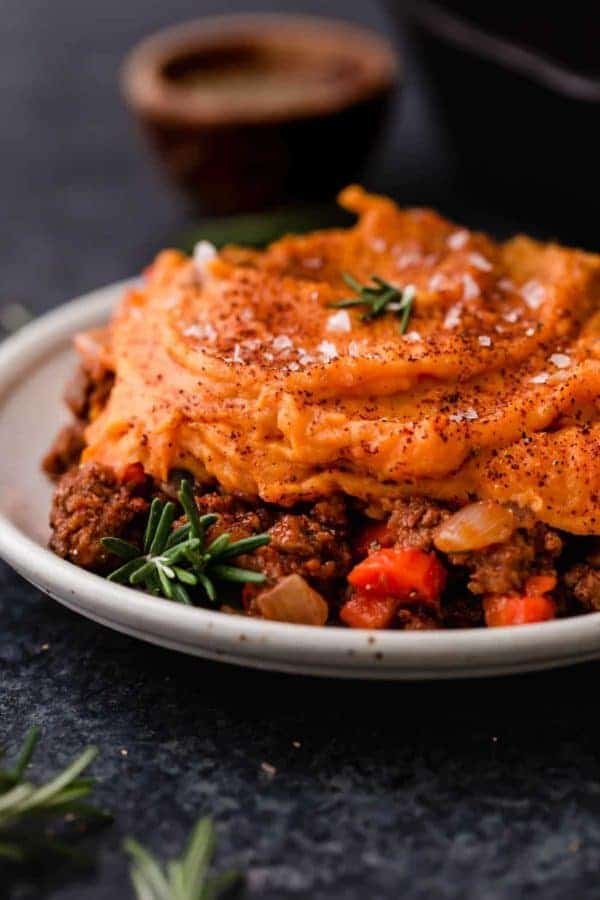 Sweet potato topped shepherd's pie on a plate with rosemary as garnish