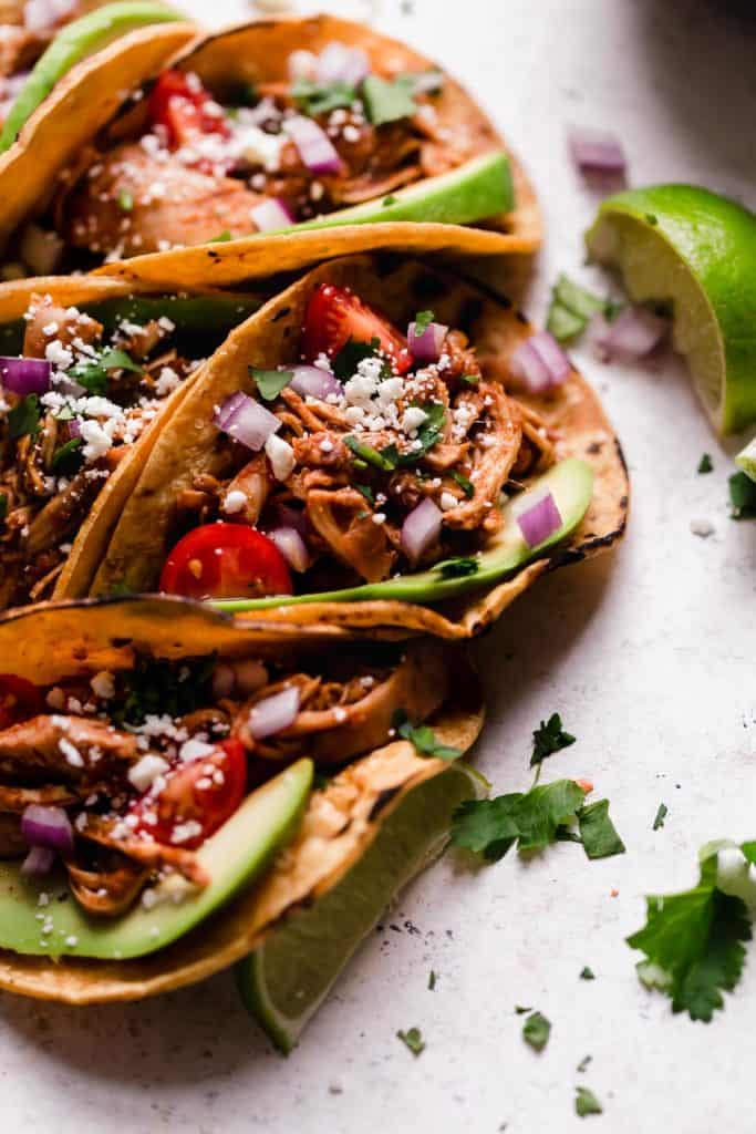 Crockpot shredded chicken tacos in crispy corn shells and topped with tomatoes, avocados, and feta cheese