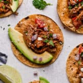 Slow cooker shredded chicken taco meat in a corn tortilla with a large avocado slice and fresh cilantro