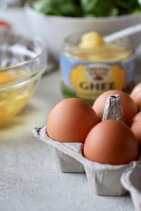Close up photo of eggs with ghee in the background. Ingredients for Turkey Sausage Sweet Potato Egg Bake