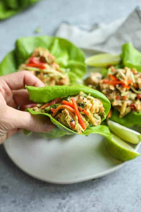 Asian Chicken Salad Lettuce Wraps on a white plate with one being picked up
