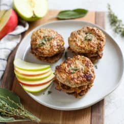 Turkey sausage patties on a white plate with a side of sliced apples