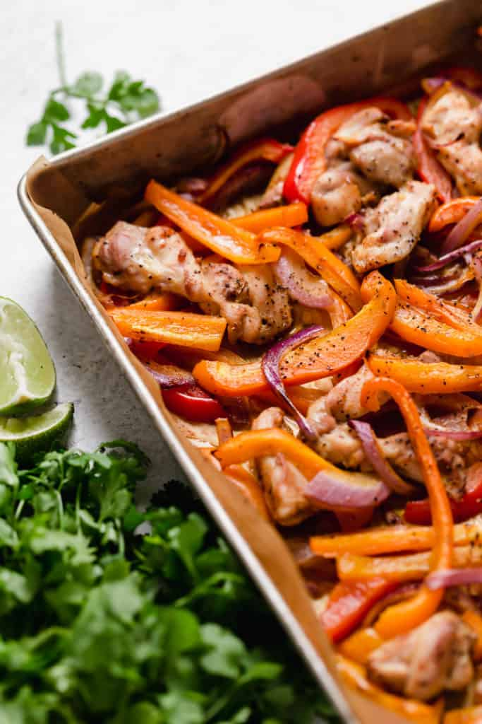 Sheet pan of cooked marinated fajita chicken, onions and peppers with lime and cilantro garnish and napkin on white surface