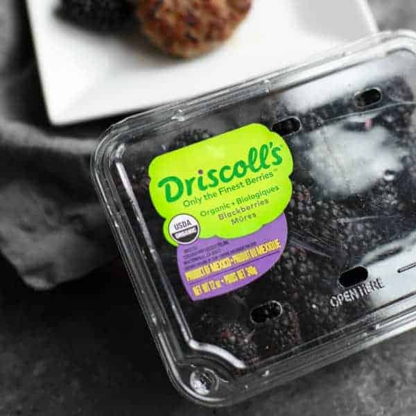 Driscoll's organic blackberries in front of a plate of Blackberry Sage Breakfast Sausage