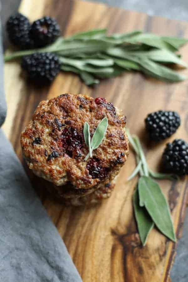 Blackberry Sage Breakfast Sausage on a wood cutting board with berries and sage