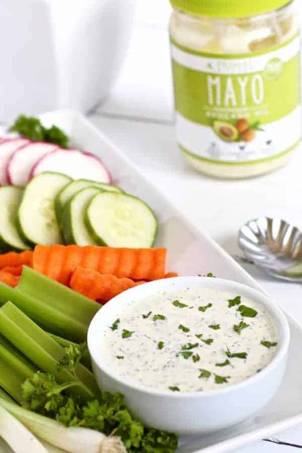 Paleo Ranch Dressing in a white bowl with vegetable dippers