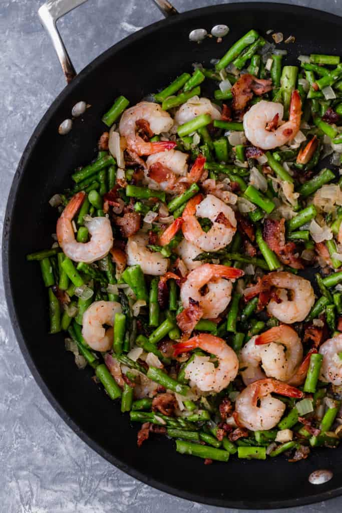 asparagus and shrimp in a cast iron skillet
