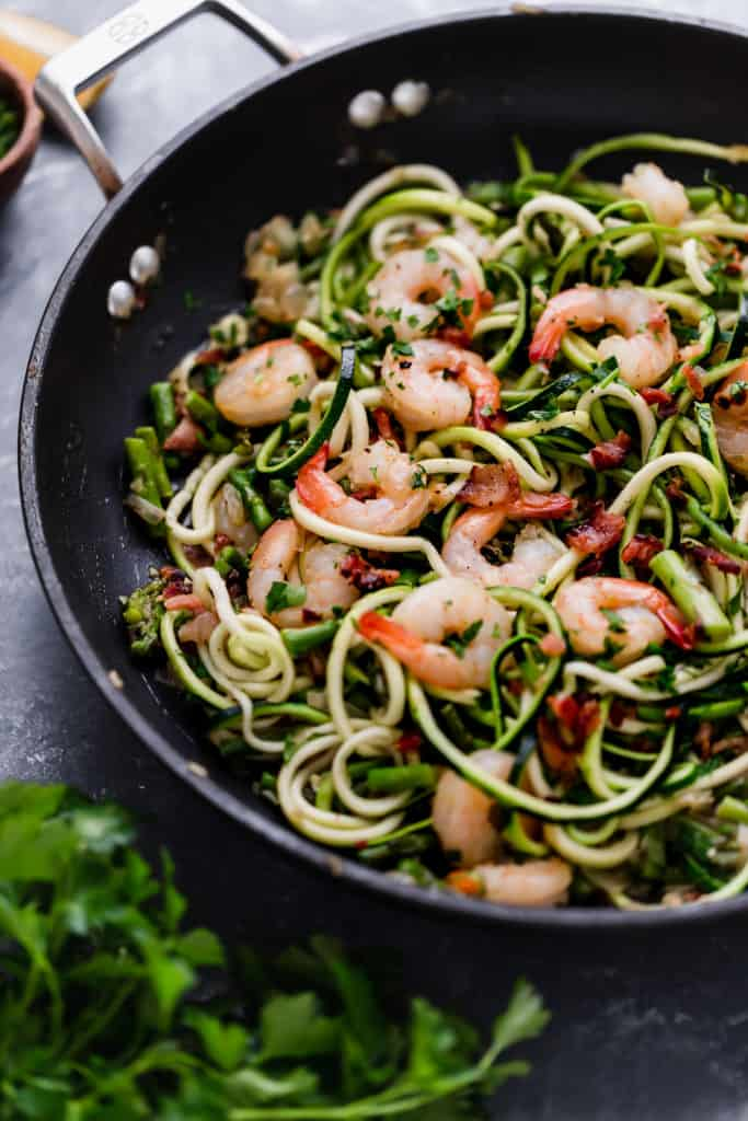 Cast iron skillet with zucchini noodles, asparagus and shrimp with garnish