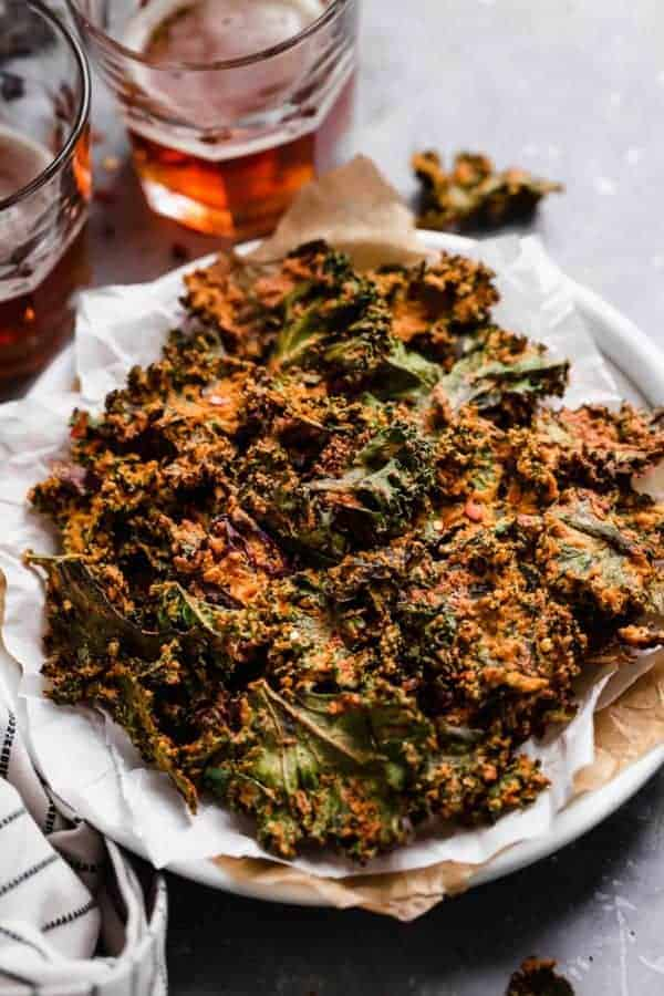 Photo of Cheese Pizza Kale Chips on a plate with two glasses of beer in the background.