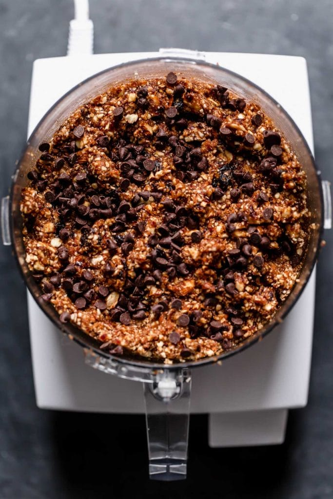 In a food processor, all ingredients for cherry chocolate energy bites ready for rolling out.
