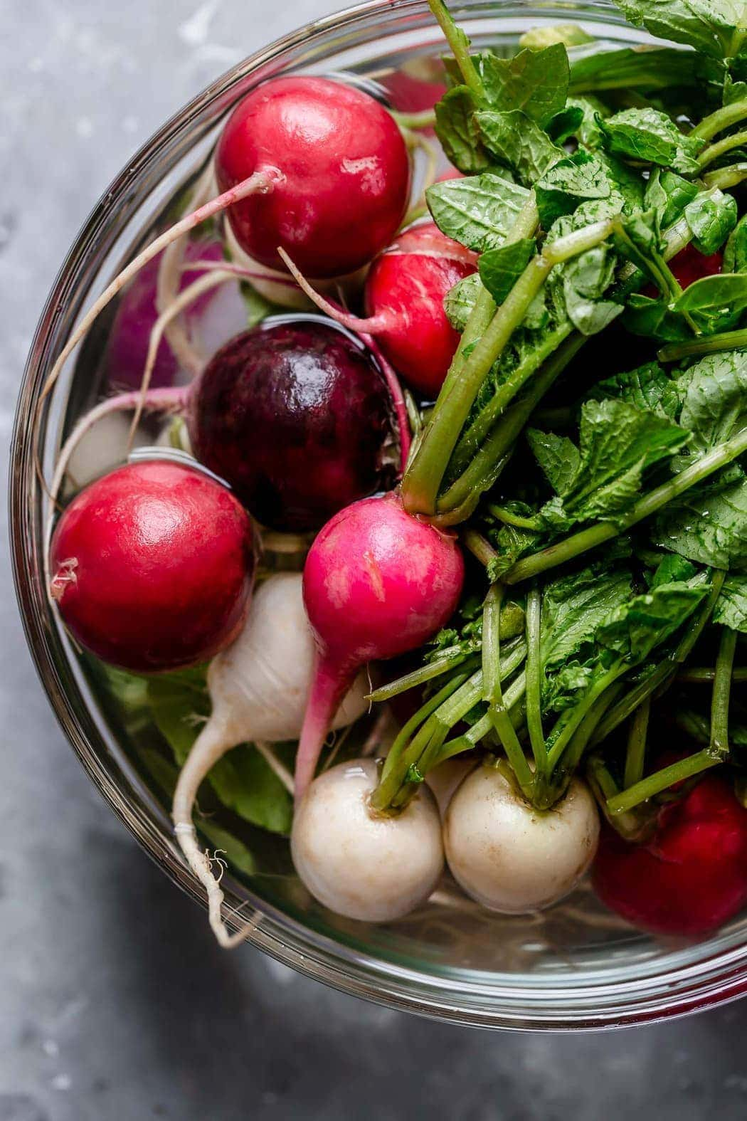 Fresh radishes with greens in a clear bowl filled with water. For the Garlic Roasted Radishes.