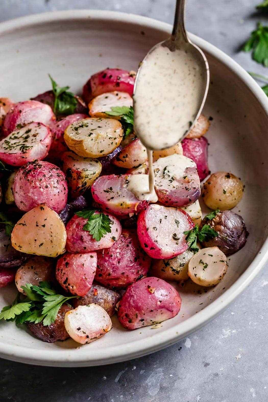 Photo of Garlic Roasted Radishes in a serving bowl being drizzled with a ranch.