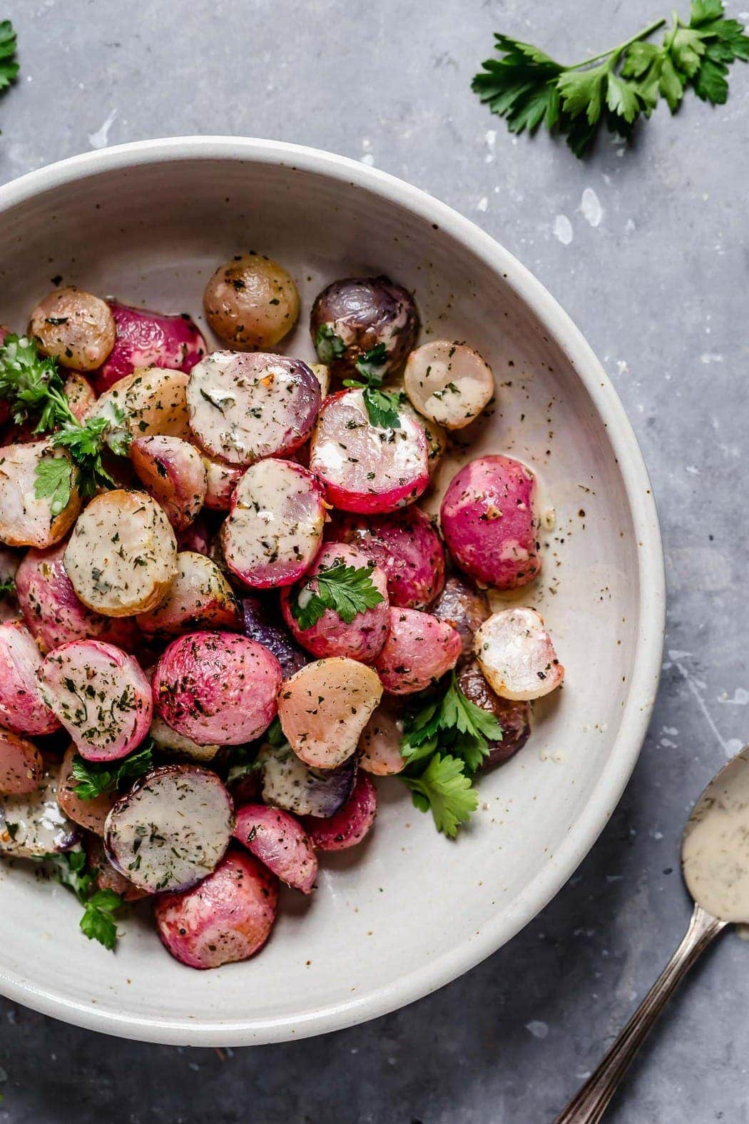 Photo of Garlic Roasted Radishes in a serving bowl with ranch drizzled over top.
