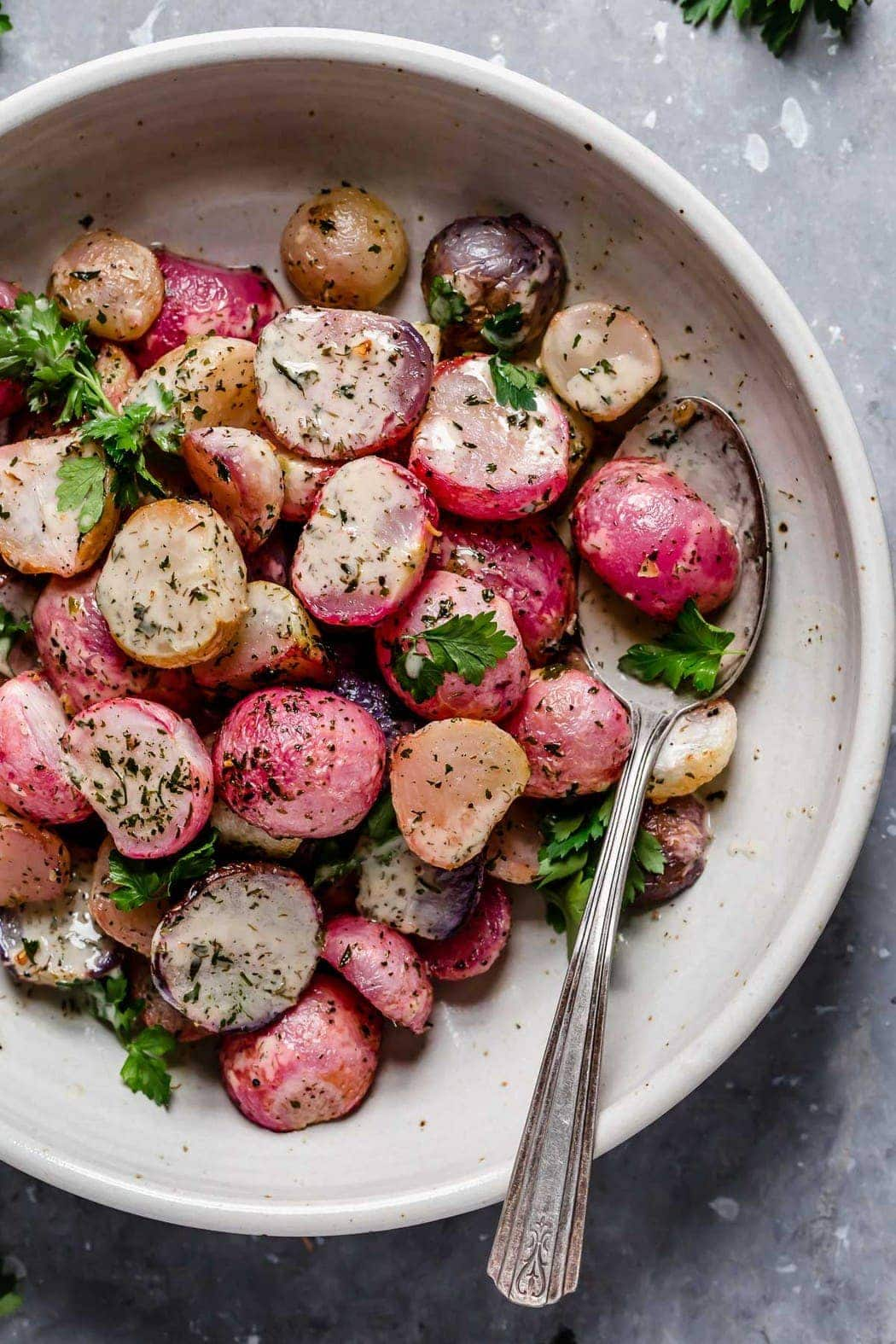 Garlic Roasted Radishes in a cream serving bowl topped with fresh herbs and homemade ranch dressing.