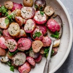 Garlic roasted radishes plated on a cream plate topped with ranch dressing and fresh herbs