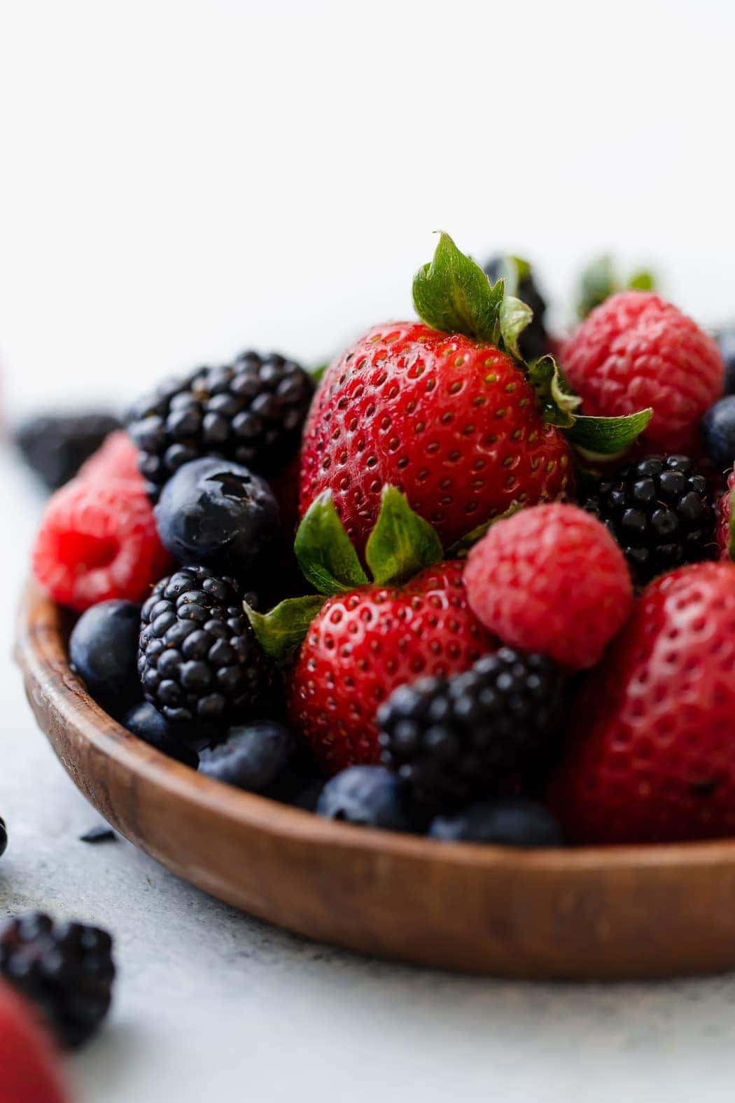 Close-up photo of a wooden plate with an assortment of berries.