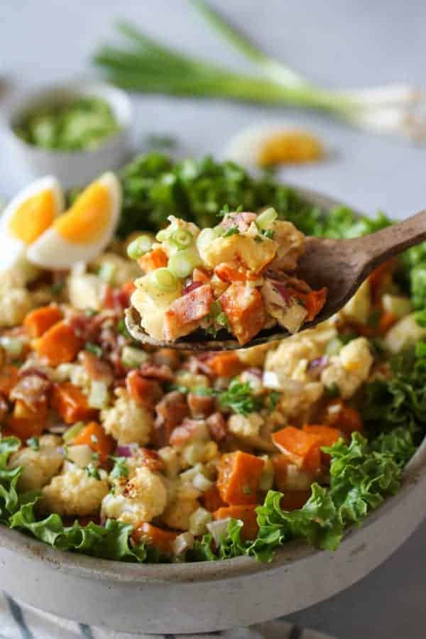 Roasted Cauliflower Sweet Potato Salad in a bowl with some on a wooden spoon being lifted towards the camera