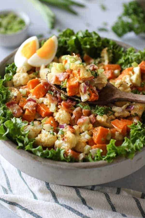 Cauliflower Sweet Potato Salad with Bacon in a bowl and on a wooden spoon resting on top