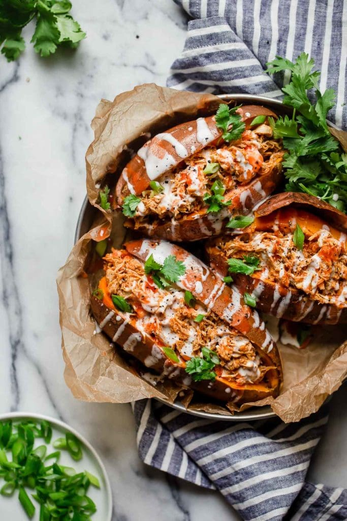 Three whole30 shredded buffalo chicken stuffed sweet potatoes drizzled with ranch in a silver pan with parchment paper under it