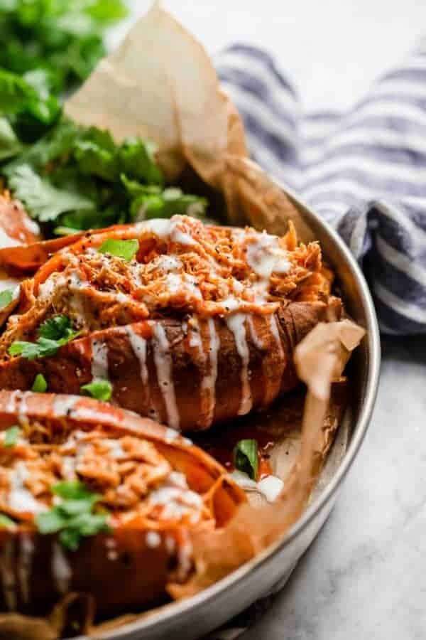 Slow Cooker Buffalo Chicken Stuffed Sweet Potatoes drizzled with ranch in a silver pan