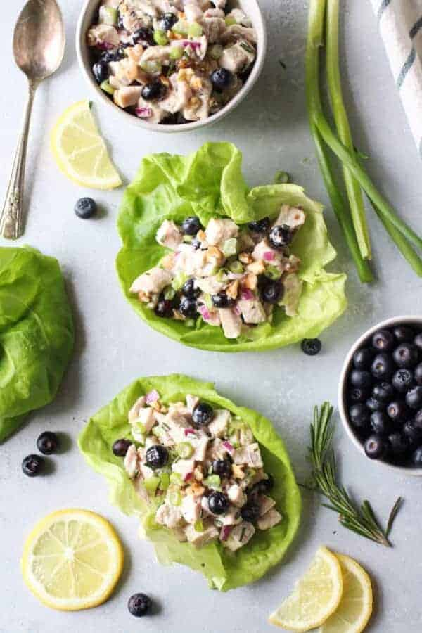Blueberry Chicken Salad with Rosemary in two lettuce wraps with additional salad in a white bowl