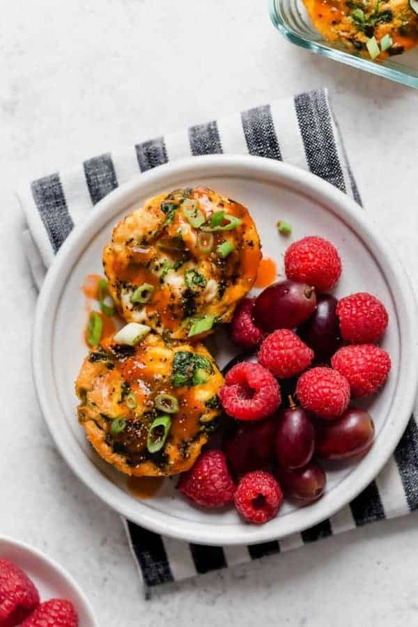 Two egg muffins served on white plate setting atop striped napkin, splashed with buffalo sauced and garnished with raspberries and grapes