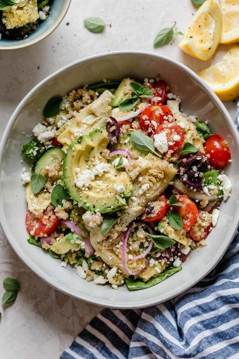 Photo of Greek Quinoa Salad with Avocado in a light gray bowl.