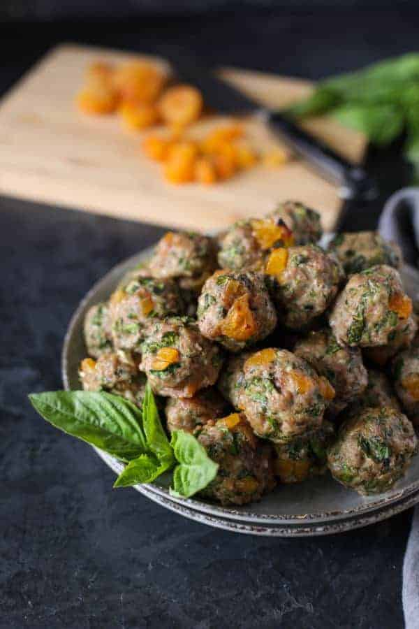 Apricot-Basil Breakfast Meatballs in a white bowl with apricots diced on a cutting board in the background