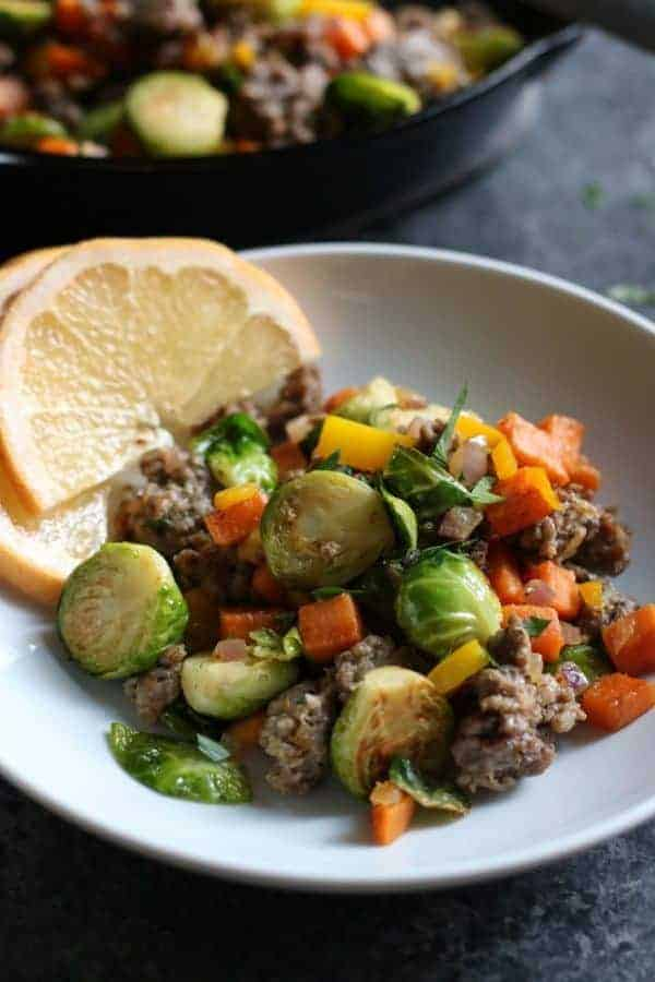 Brussels Sprouts Sweet Potato Hash in a white bowl with orange slices