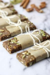 Pumpkin Spice Protein Bars lined on a counter wrapped in paper and tied with a string bow