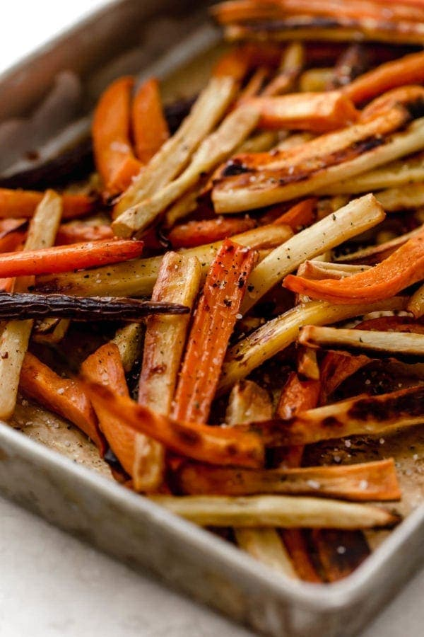 Close up of a sheet pan with garlic roasted root vegetable fries hot from the oven.