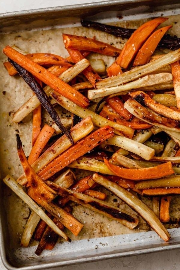 Overhead view of a pan of garlic roasted root vegetable fries sprinkled with coarse sea salt.