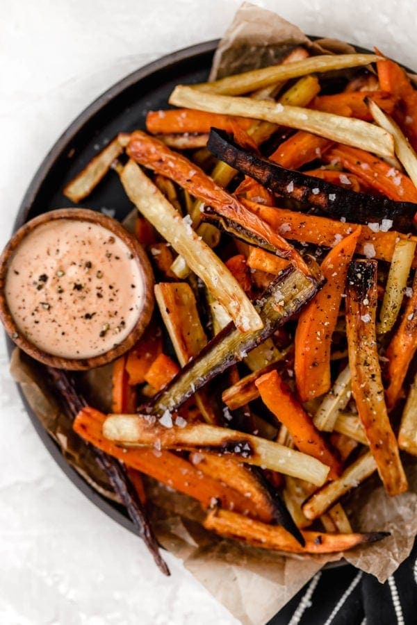 Overhead view of a plate of garlic roasted root vegetable fries with a side of dipping sauce.