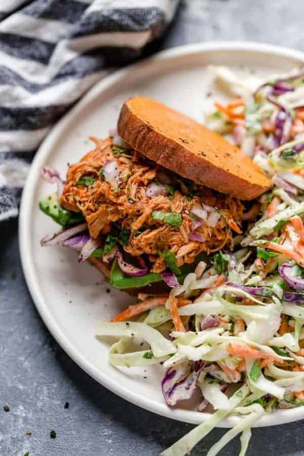 Overhead view of Slow Cooker Chicken Sloppy Joe Sliders with a side of slaw on a white plate