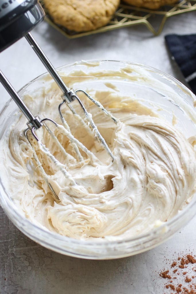 Cream cheese frosting in a glass bowl with beaters in the frosting