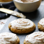 Several pumpkin cookies on a slate serving tray topped with cream cheese frosting